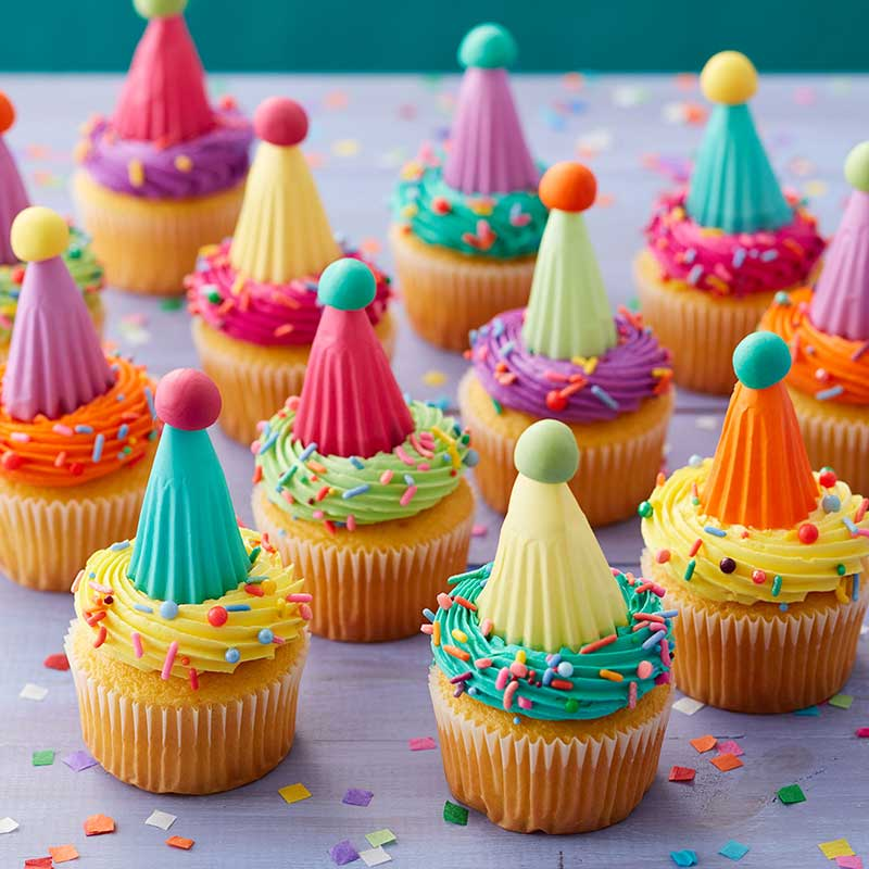 Colorful party hat cupcakes made using baking cups as the party hats