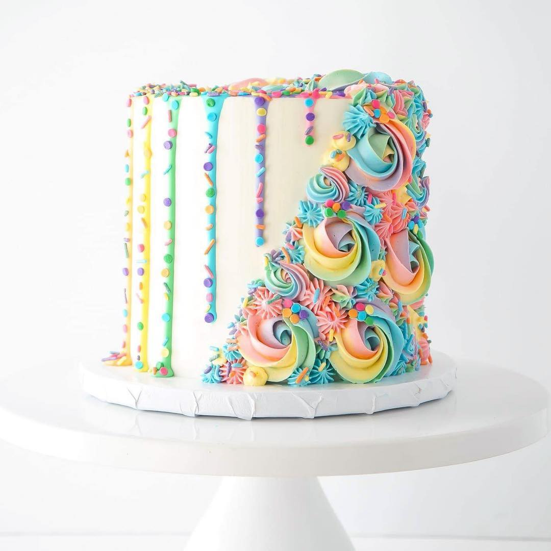 White cake decorated with rainbow pastel buttercream swirls on half the cake and rainbow drips covered in sprinkles on the other half.