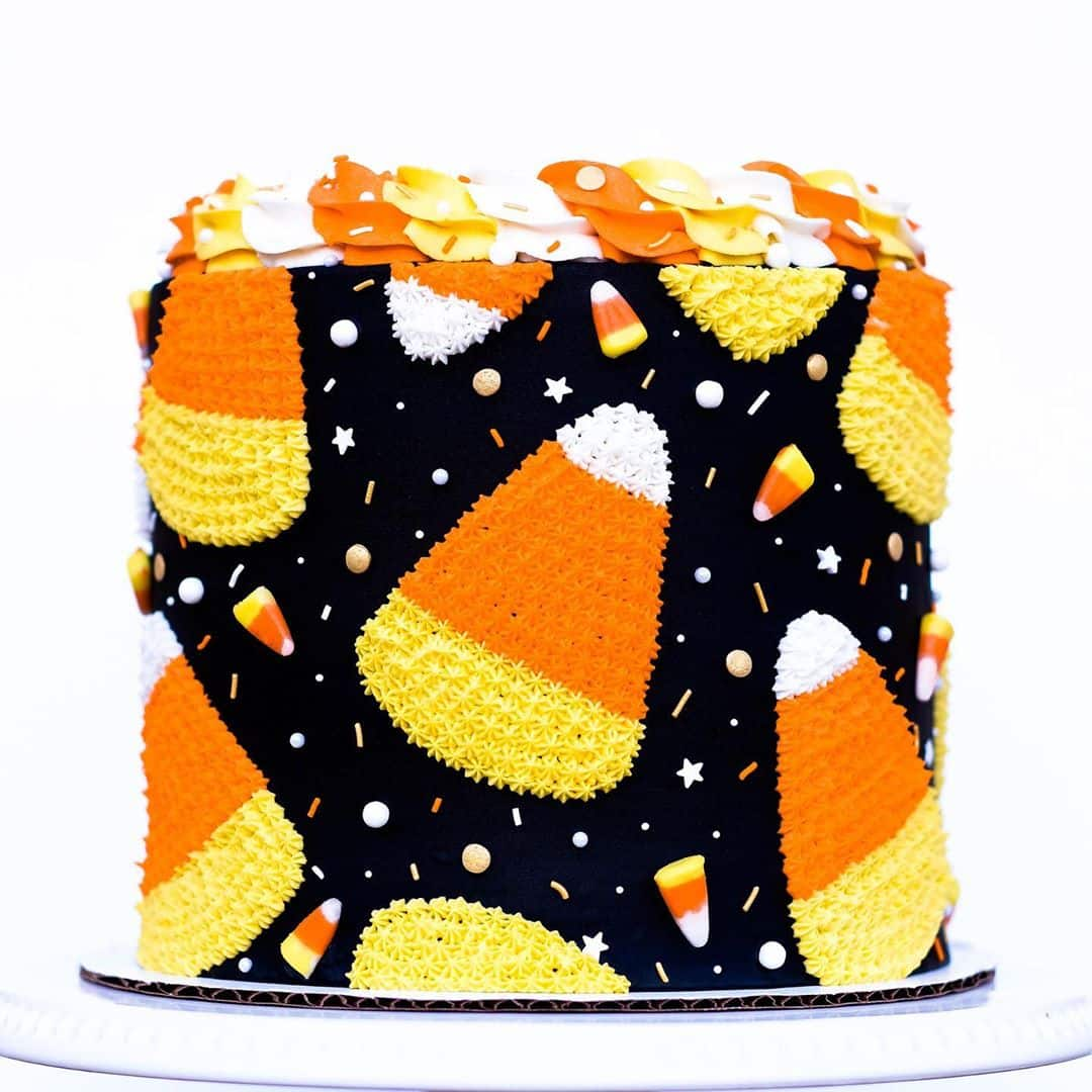 Black cake decorated with large piped candy corns and candy corn candy and sprinkles covering the sides. Topped with orange, yellow, and white frosting on top.