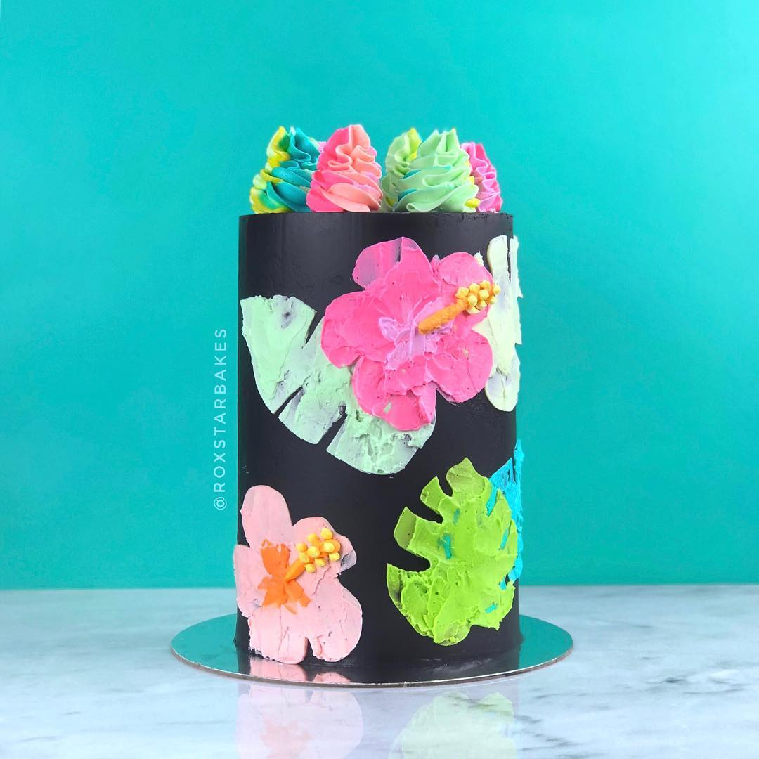 Black cake with shades of pink Hawaiian flowers and green palm leaves. Topped with frosting swirls in pink and green.