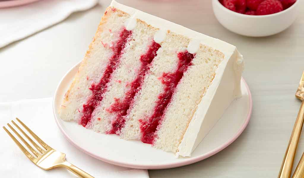 raspberry filled cake frosted with white buttercream frosting on a plate