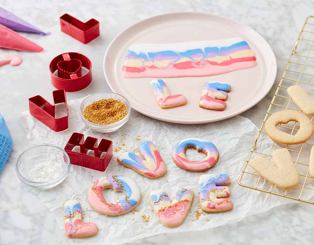 Sugar cookies cut out spelling love and decorated with pastel pink, blue and white icing