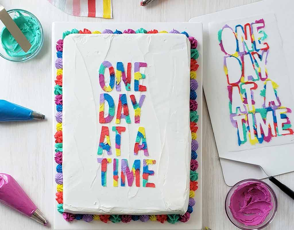 white buttercream frosted cake with the words one day at a time decorated on top in multiple colors