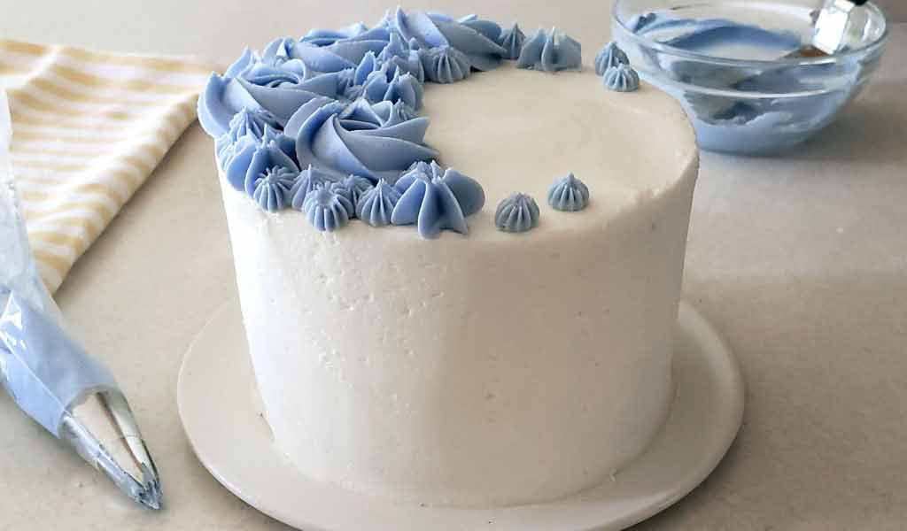 cake frosted with a crusting buttercream frosting and decorated with blue buttercream flowers