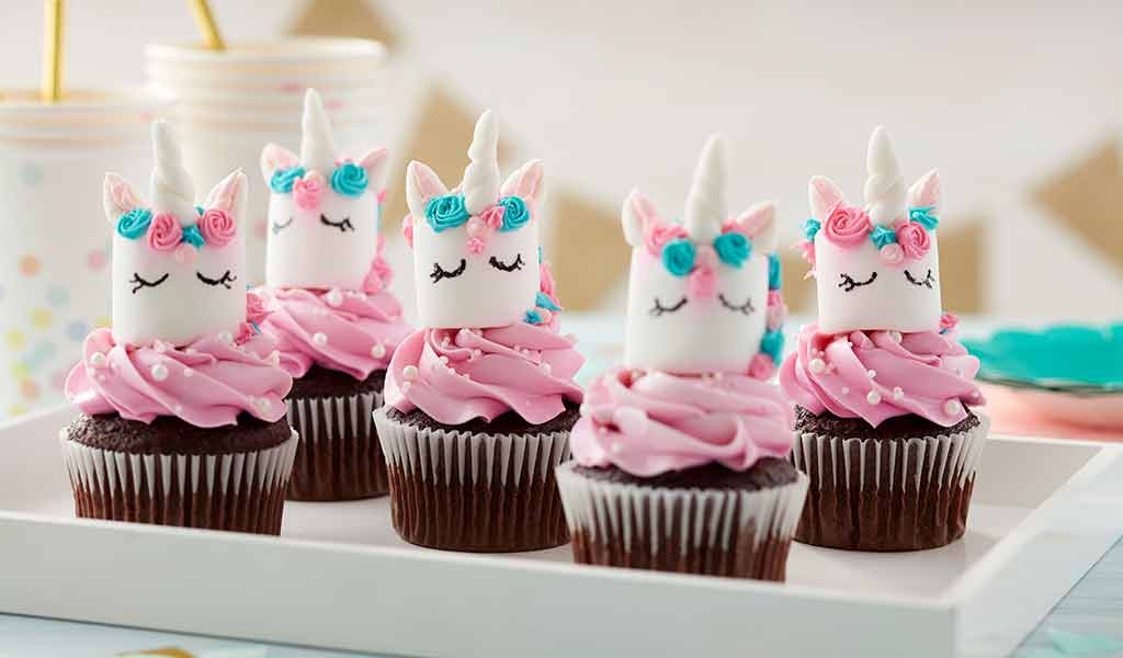 chocolate cupcakes with pink buttercream frosting and marshmallows decorated as unicorns