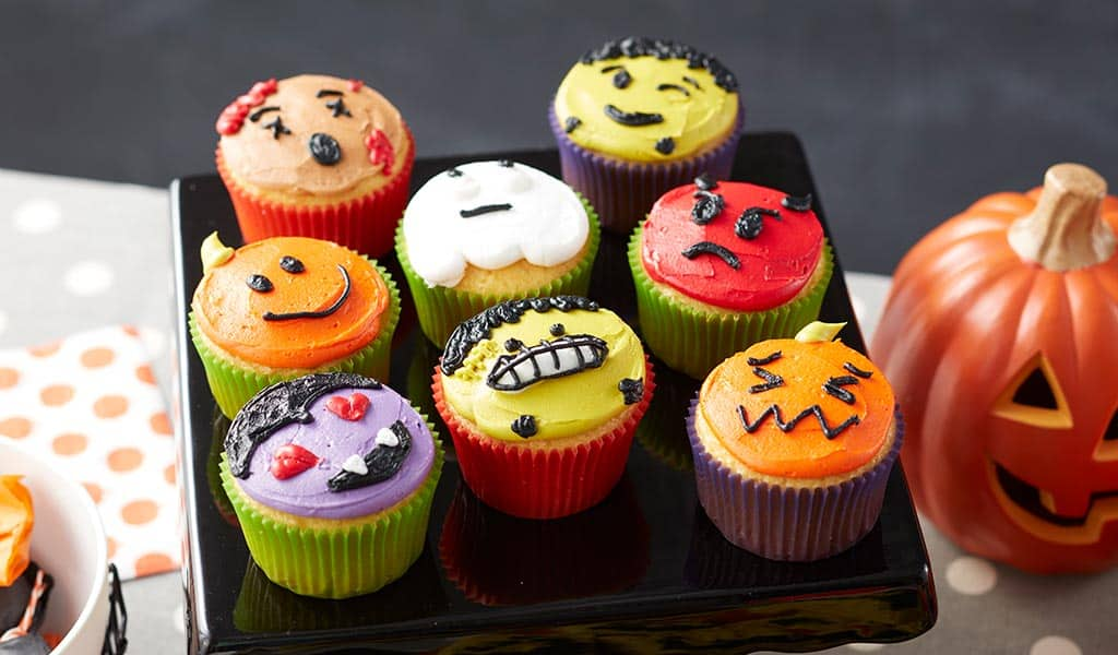 Cupcakes decorated like Halloween Emojis - Dracula with heart eyes, Frankenstein face, pumpkins, ghost, and red devil.