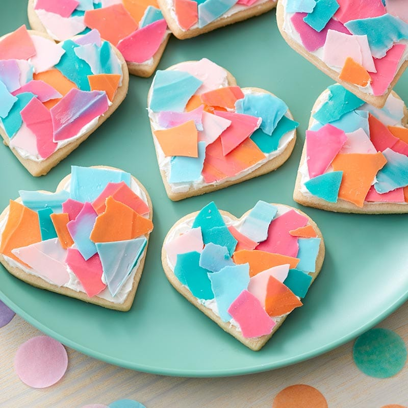 Heart-shaped cookies with Candy Melt pieces topping them to look like confetti