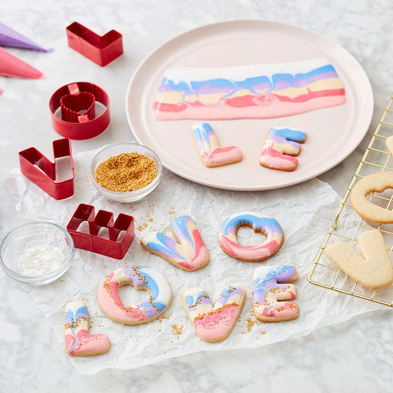 L-O-V-E cookies decorated with white, blue, and pink royal icing