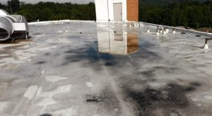 Standing water on a roof with deteriorating roofing membrane and dirt