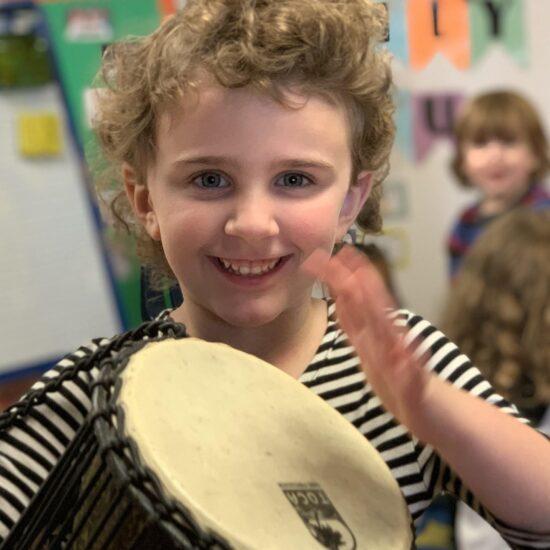 Girl playing talking drum