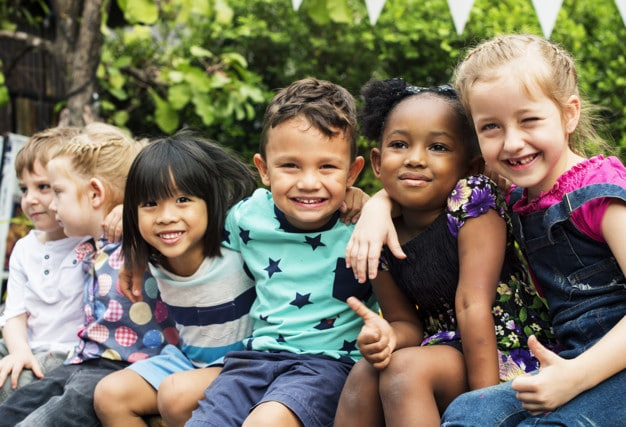 Group of kindergarten kids friends arm around sitting and smilin