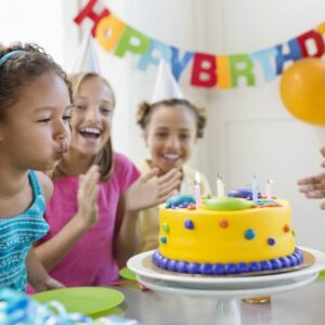 Kids blowing birthday candles.