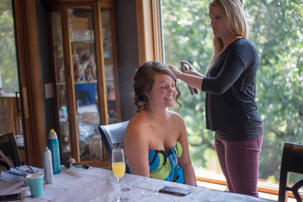 Bride having hair done on wedding day