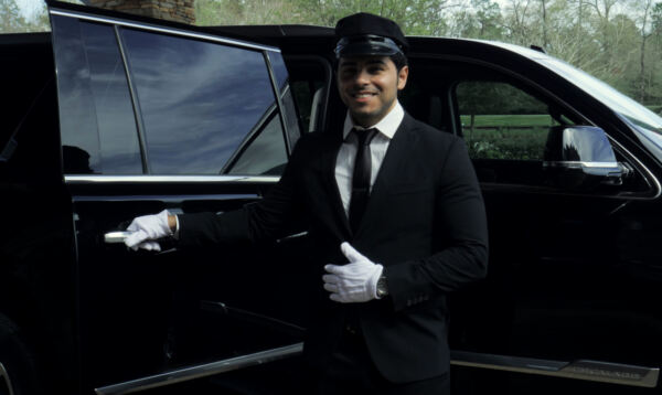 Professional and friendly limo chauffeur holding door open for passengers in The Woodlands
