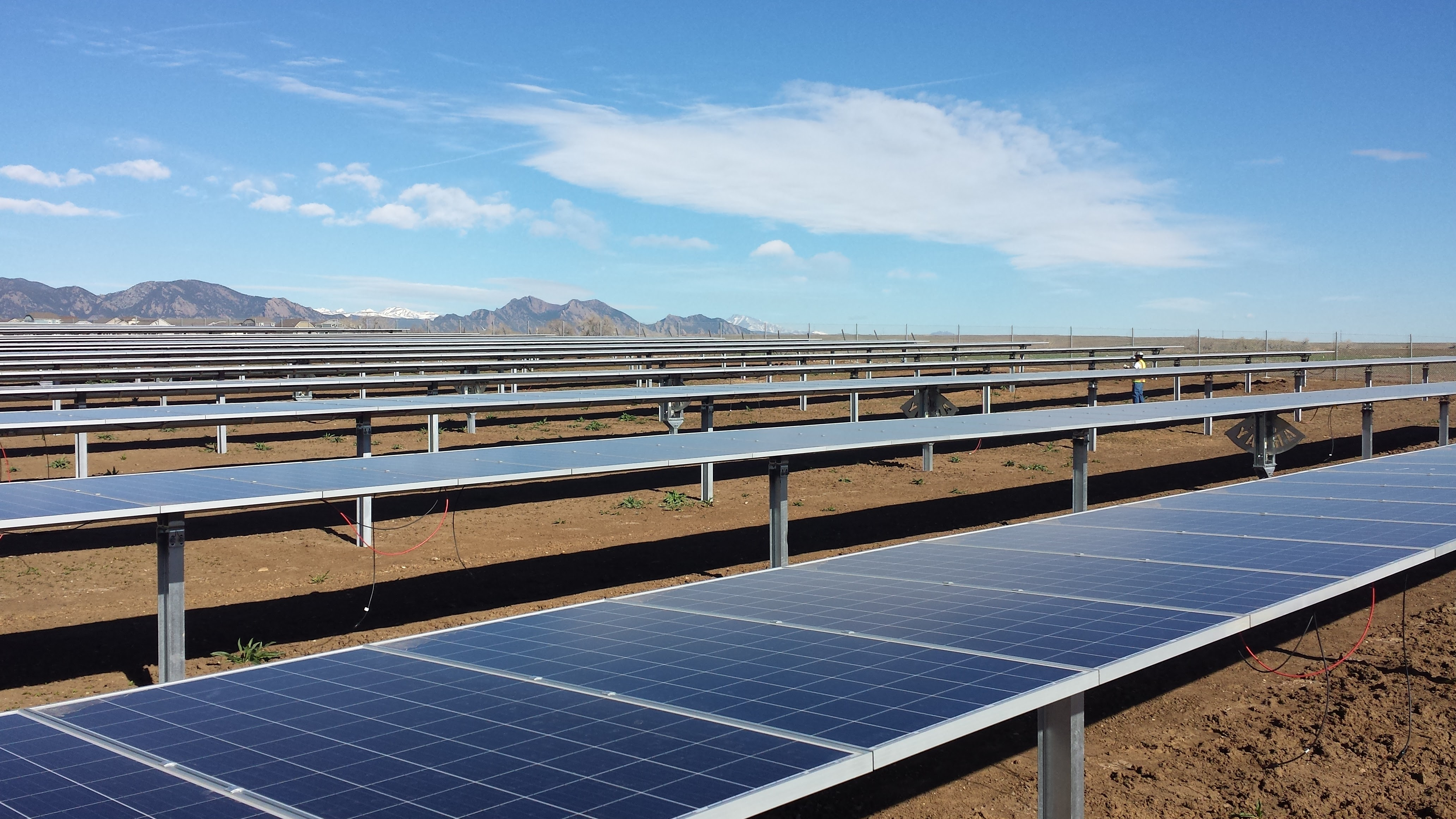 Rows of solar panels in front of mountains