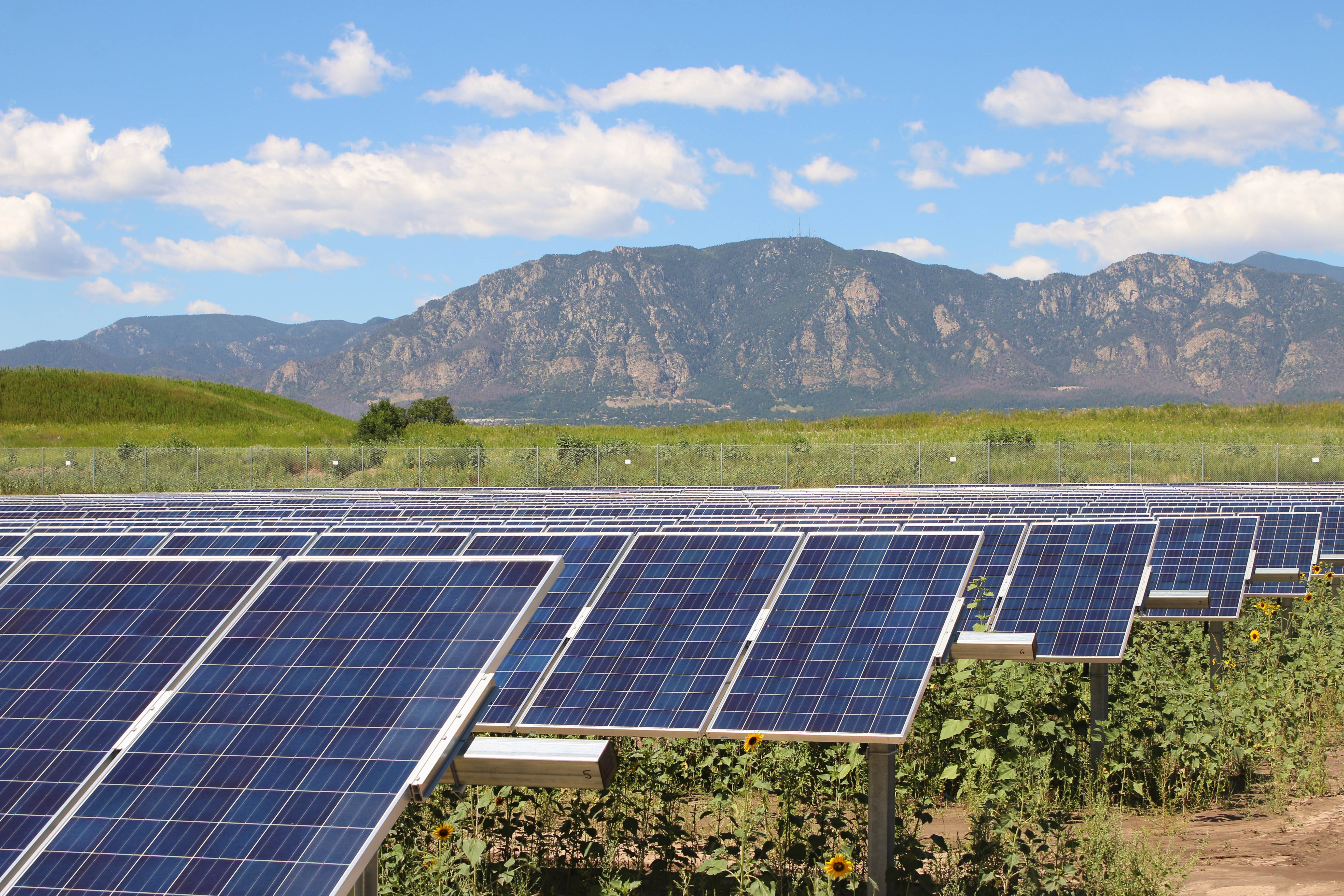 Rows of solar panels by mountains