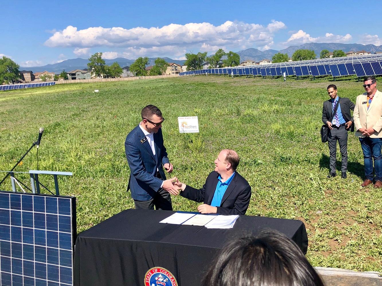 Two men shaking hands in solar panel field