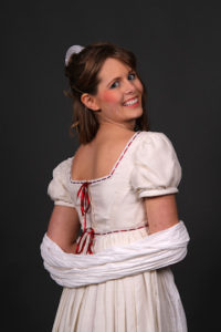 female model posing in a historical regency period empire waist dress