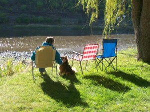 Guest in lawn chair sitting by the Salmon River at Swiftwater RV Park