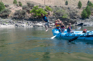 Exodus Salmon River raft in Salmon River with kids jumping into river