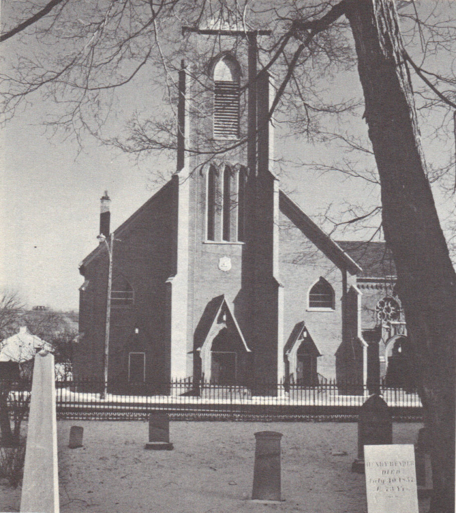 Black and white photo of front of St. Augustine's church taken from the churchyard of Trinity.