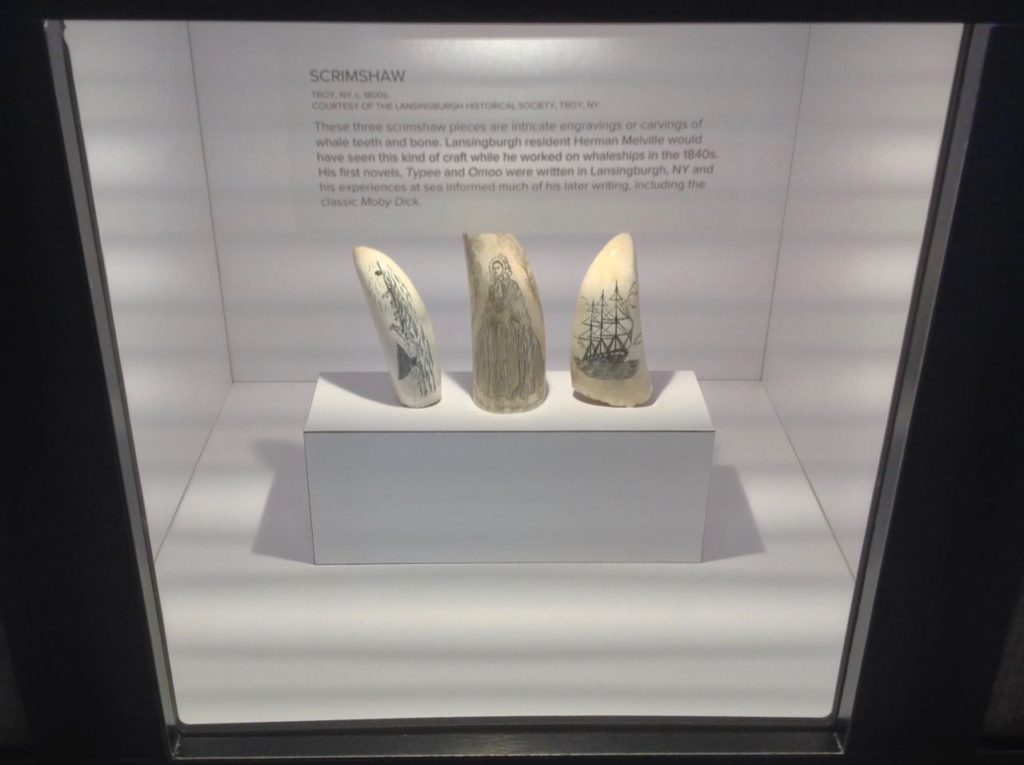 Three pieces of modern engraving on whale's teeth in a lighted cabinet, one of a whaling scene, another of a woman in fancy clothing, another of a whaling ship.