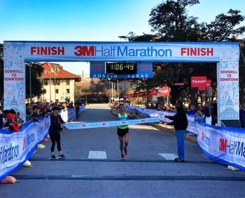 Runner crosses 3M Half Marathon finish line