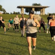 Determined woman finishing rep of a cross training exercise in Camp Gladiator