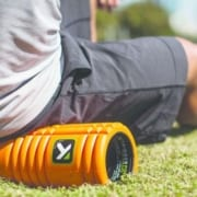 Runner is foam rolling to help muscles recover.