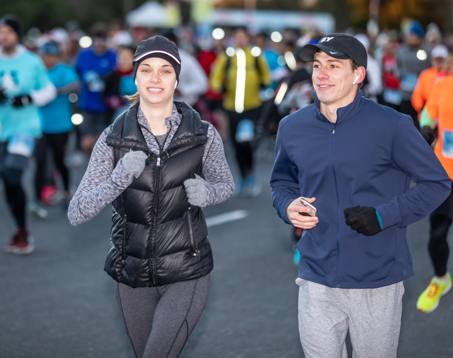 Two runners stay safe by running together and carrying their phone.