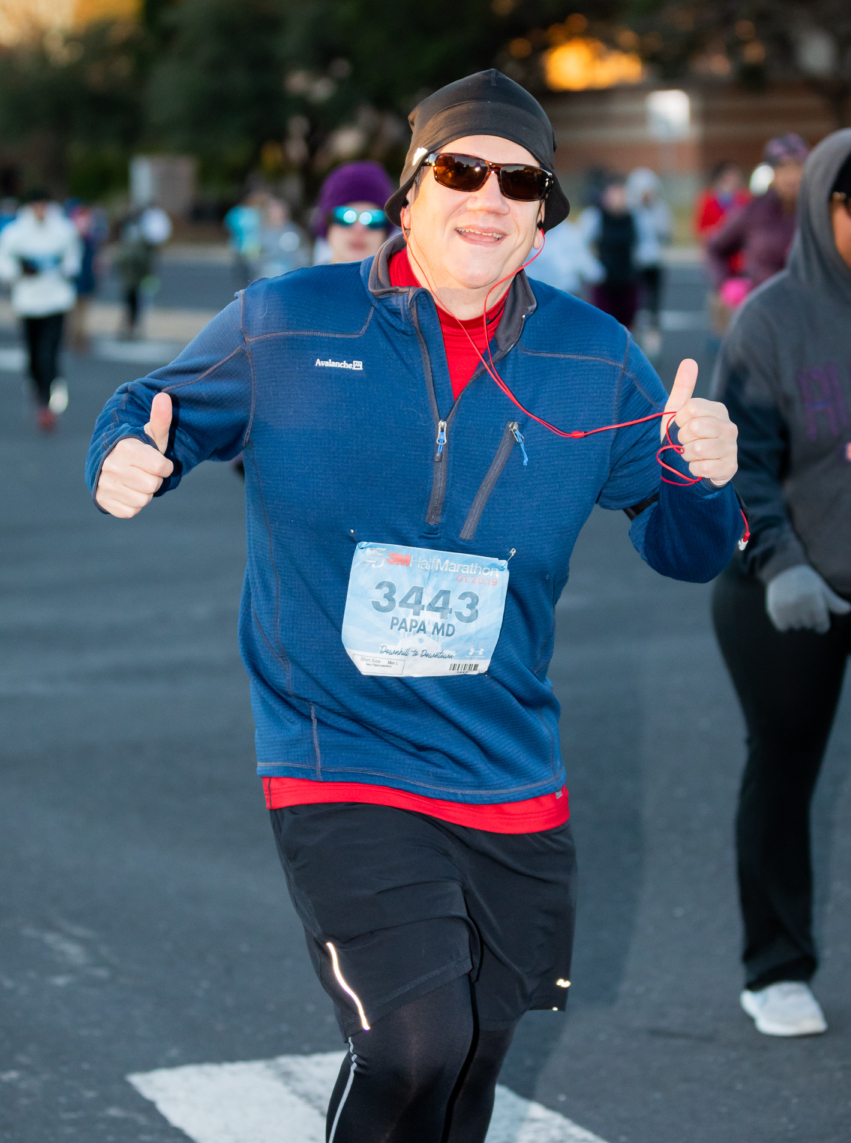 Runner gives two thumbs up during 2019 3M Half Marathon while listening to music. Runners can make their own playlist to help them get up in the morning for their morning run.