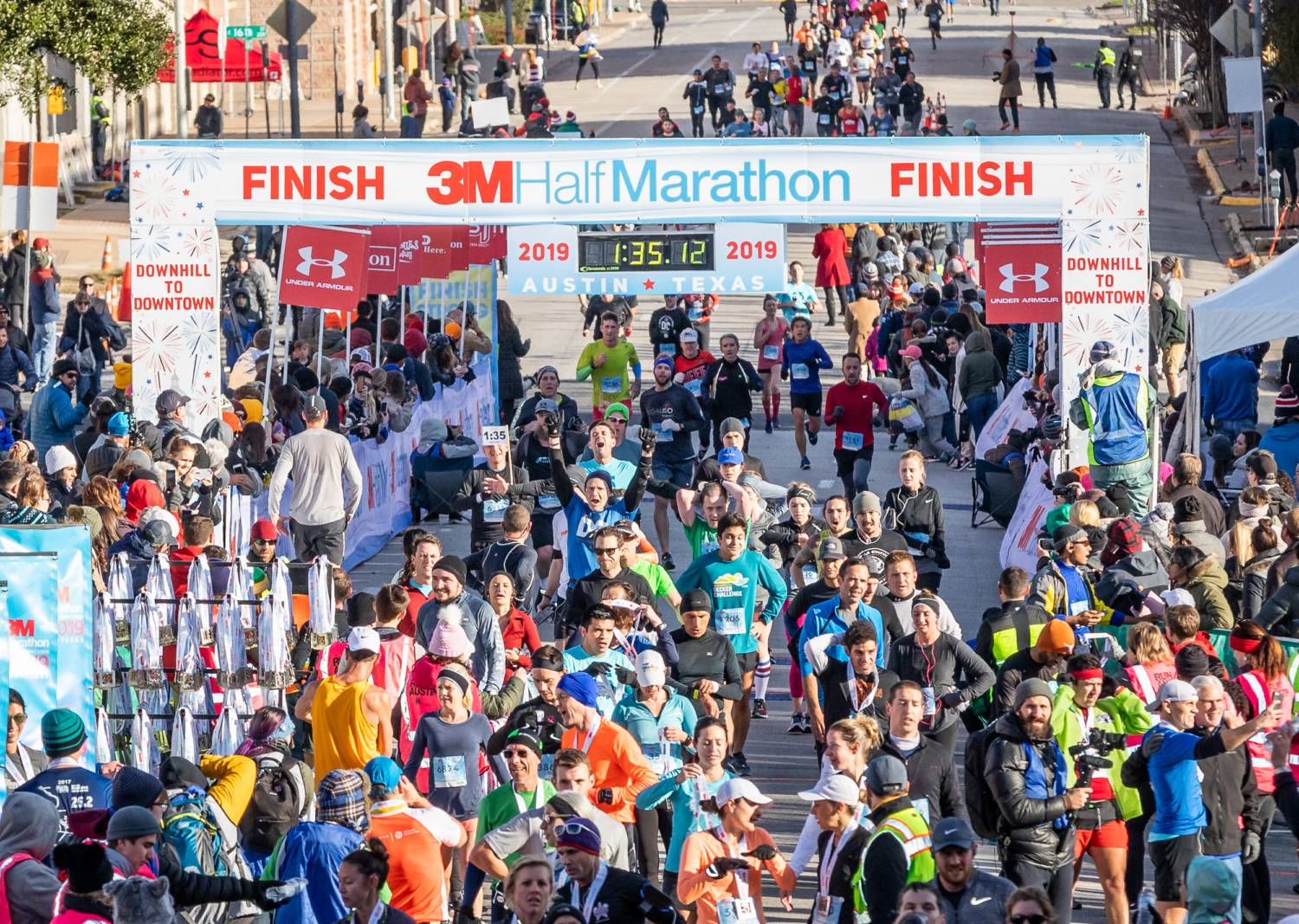 Runners cross the 2019 3M Half Marathon presented by Under Armour finish line.