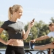 Image of female runner setting her running playlist while a male runner stretches. This 3M Half Marathon blog showcases 10 new songs for a running playlist update.