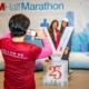 A 3M Half Marathon Ambassador takes a photo of two runners and the oversized 2019 3M Half Marathon medal at the 2019 3M Half Marathon expo. Take your photo with a giant 2020 3M Half Marathon medal, one of the many 2020 expo highlights.
