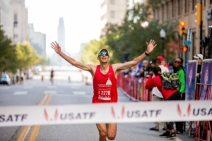 Image of Philippe Rolly with hands in the air, about to cross a finish line. Rolly will run with the 2020 elite field at the 2020 3M Half Marathon presented by Under Armour.
