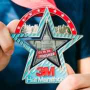 Image of two hands displaying the 26th annual 3M Half Marathon presented by Under Armour finisher medal.