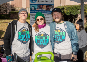 Image of 3 Austin Youth River Watch representatives at their booth at the 2019 3M Half Marathon. 3Mgives selected Austin Youth River watch as the beneficiary of the 26th annual 3M Half Marathon on January 19, 2020.