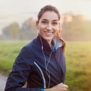 Image of runner listening to her headphones while smiling before a run. This blog has January running playlist additions for our #WeLiketheSoundofThat playlist.