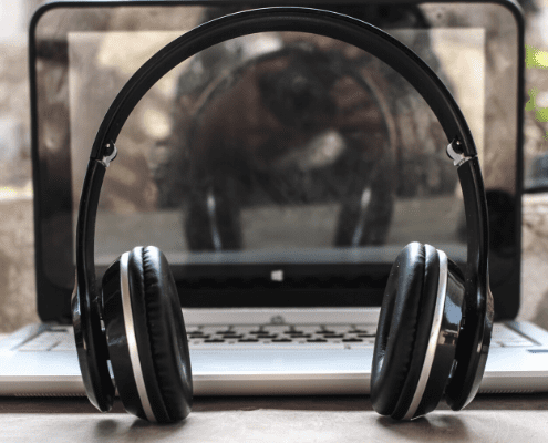 Image of headphones sitting in front of a laptop. Read this blog to learn what the staff at High Five Events would listen to forever.