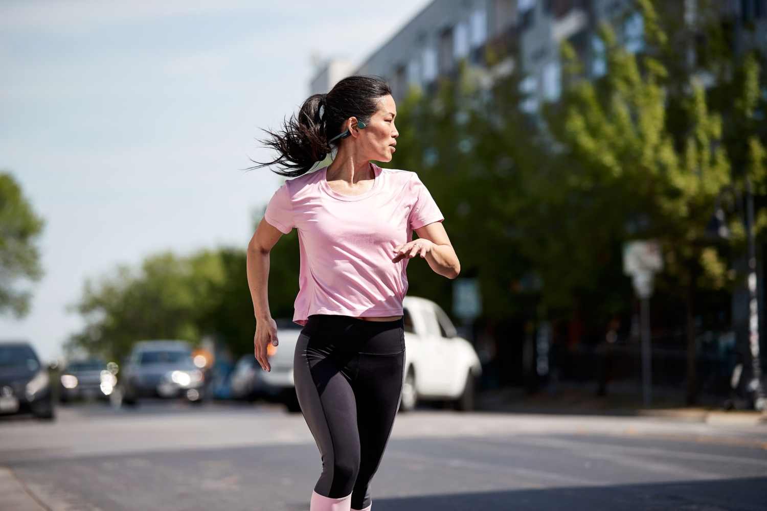Image of female running listening to Aftershokz headphones while running. She can listen to music and her surroundings, an important self-care tip in this 3M Half Marathon blog.