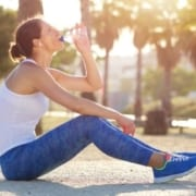 Image of woman drinking from a water bottle after a run. Proper hydration is an important self-care tip in this 3M Half Marathon blog.