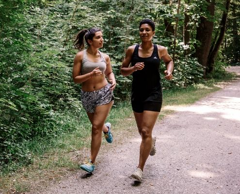 Image of two women running on a shaded trail. They're following the 3M Half Marathon's summertime running advice to beat the heat while they run.