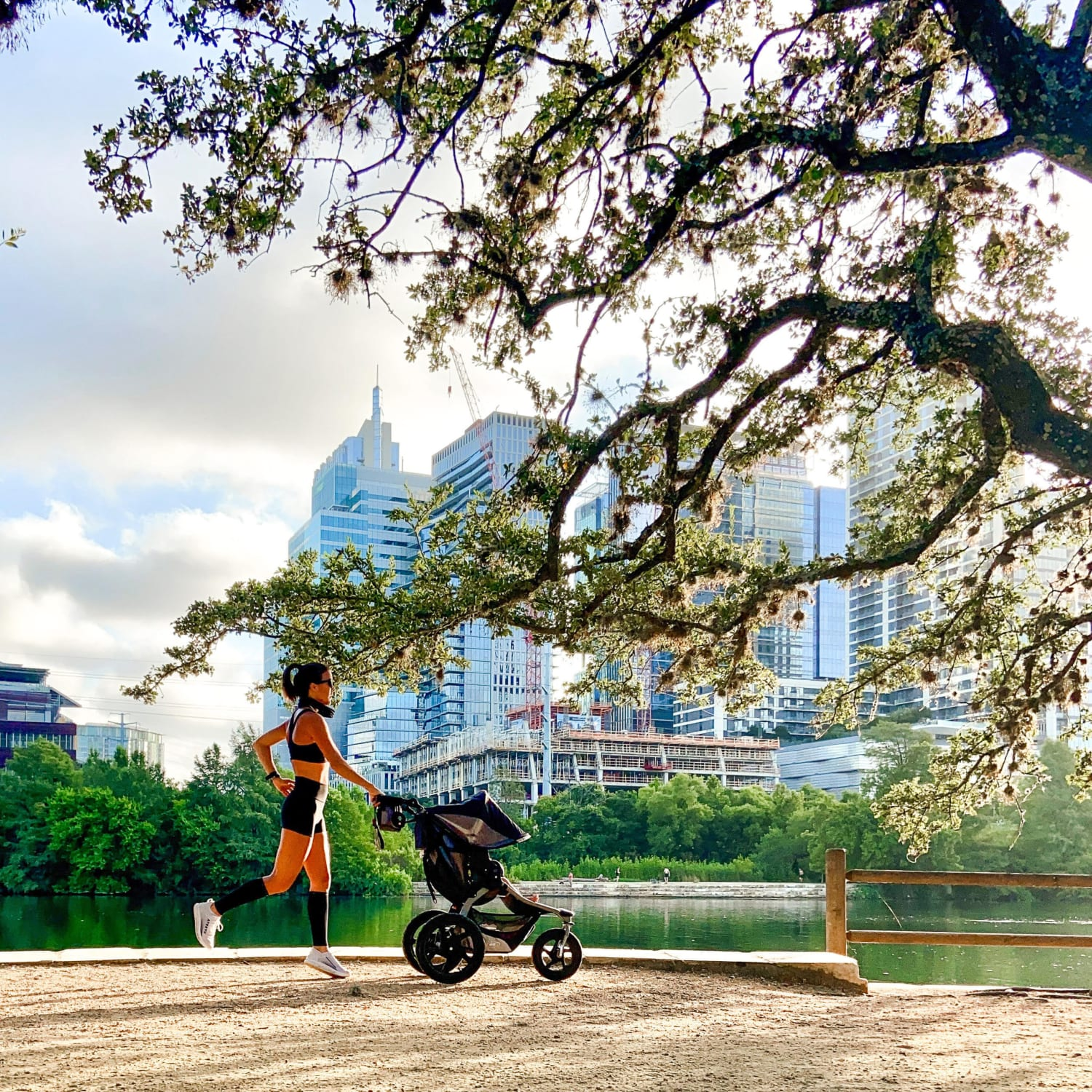 Image of Samantha, a runner and a mother, running with a stroller on the Town Lake Trail with the Austin skyline in the background. She contributed some of the information in this blog about how to run with a stroller.