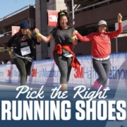 Three female runners excitedly cross the 2020 3M Half Marathon finish line while holding their hands in the air. Selecting the right running shoes for you will help you reach the finish line. Read more at https://downhilltodowntown.com/right-running-shoes-for-you/