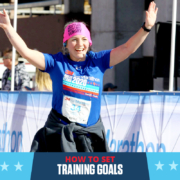 Female runner crosses the 3M Half Marathon with her arms raised triumphantly in the air. Text on design reads How to Set Training Goals. Learn more at https://downhilltodowntown.com/set-training-goals/