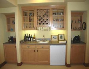 Photo of maple wood wet bar and cabinets in a home