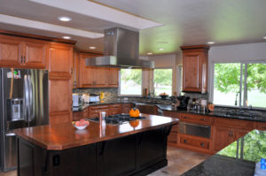 Photo of custom cherry wood kitchen cabinets and island