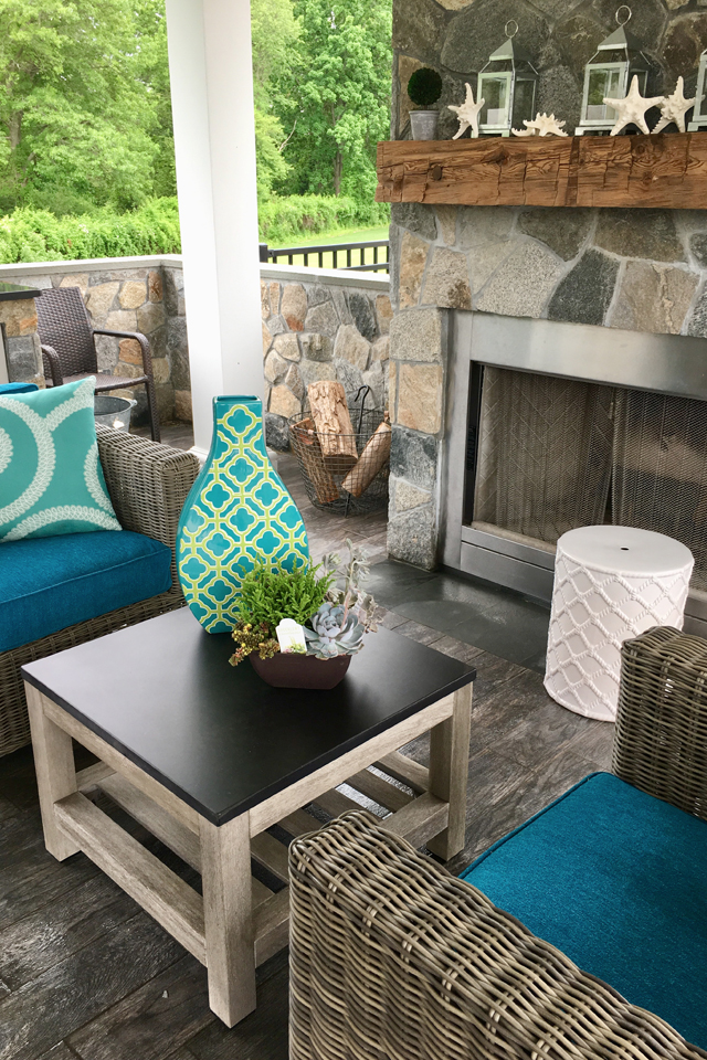 outdoor fireplace surrounded by attractive furniture and decor