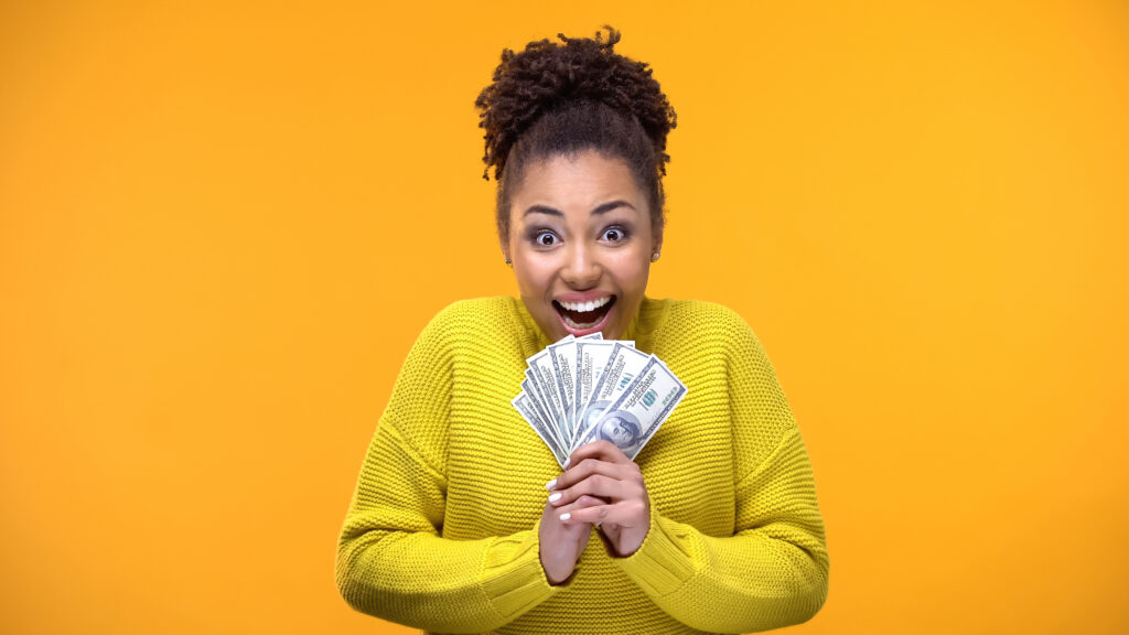 Excited woman holding bunch of dollars, lottery winner, fortune
