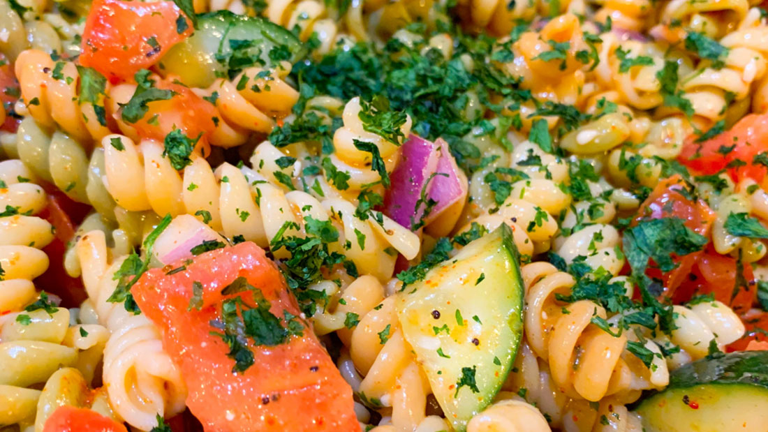 close up of colorful pasta salad with cucumbers and tomatoes